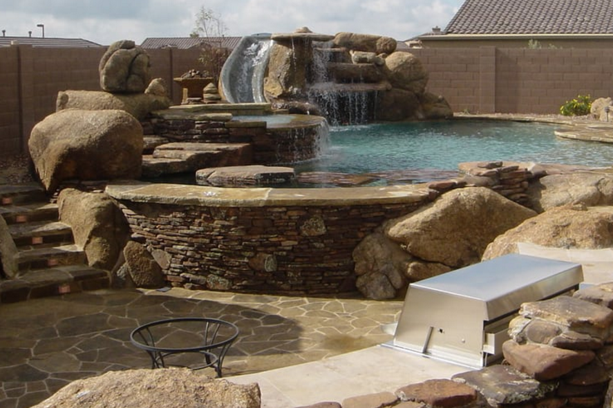 Flagstone_decking_rock_waterfall_with_boulder_replacement_and_BBQ_Island