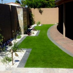 Artificial_turf,_paver_patio,_charcoal_border,_white_marble_rock,_plants._Entire_backyard_designed_and_installed_by_Envirogreen_Landscape
